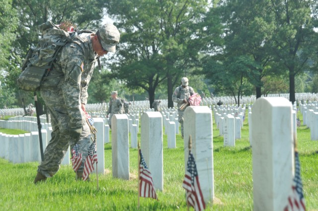 Soldiers assigned to Bravo Company, 3d U.S. Infantry Regiment (The Old Guard) place American flags in front of fallen veterans grave stones.