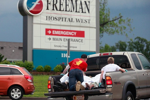 Lucian Myers, wearing a red Pittsburg State University T-shirt, assists injured people just after a deadly tornado struck Joplin, Mo.