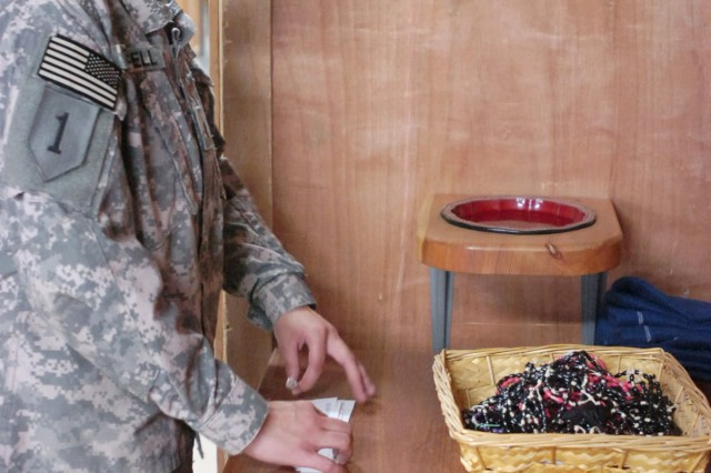 CONTINGENCY OPERATING SITE WARRIOR, Iraq – Spc. Faith Bedwell, chaplain assistant, Company C, 101st Brigade Support Battalion, 1st Advise and Assist Task Force, 1st Infantry Division, arranges items on a table at Freedom Chapel, Contingency Operating Site