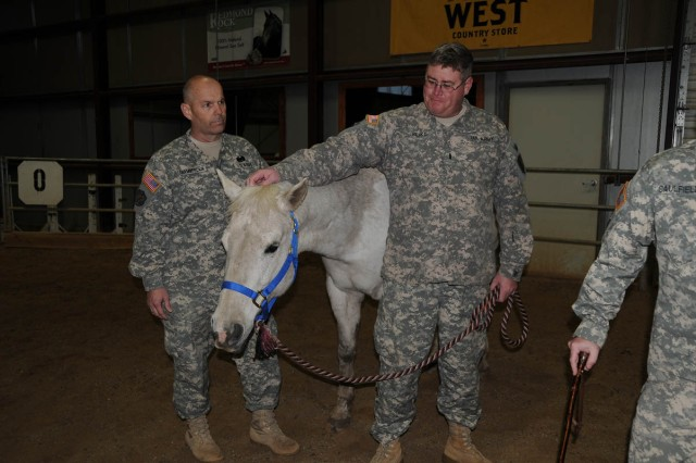 1st Lt. Cliff Slike, Colorado Army Reserve, and Staff Sgt. Michael Chamberlain, New Mexico Army Reserve, pet Soda, just before finishing Equine Facilitated Learning at the Community Based Warrior Transition Unit-Utah muster May 17 at the National Ability