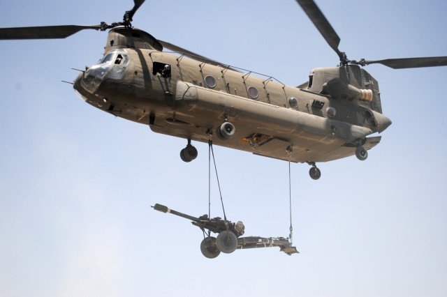 A Chinook helicopter carries an M119 howitzer to Soldiers of Battery A, 1st Battalion, 6th Field Artillery Regiment, 3rd Brigade Combat Team, 1st Infantry Division, Task Force Duke, at their mountain outpost in Khowst province, Afghanistan.