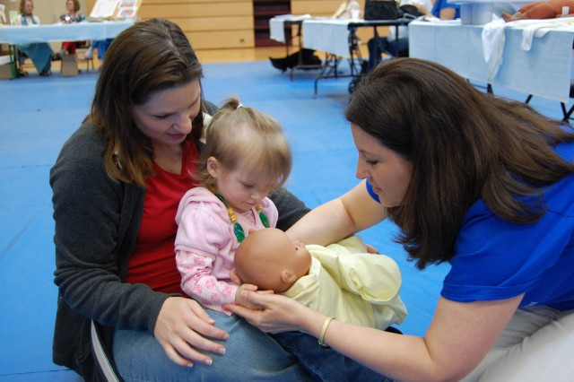 Registered nurse Pamela Krings, with New Parent Support Program, Army Community Service Family Advocacy, shows a 2-year-old how to hold her future sibling as mom Laura Cashion looks on, at the Mannheim Community Baby Shower at the Sports Arena in Mannheim