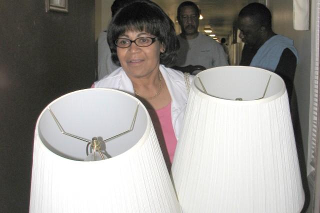 Helen Crockett, wife of retired Air Force Master Sgt. Wayne Crockett, carries away two lamps.
