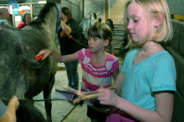 "Ten-year-old Danica Slater and 8-year-old Kissanne Calkins groom ""Cherokee"" during the EDGE! Saddle Up program at the Fort Leavenworth, Kan., stables. Children learn about grooming, tack and more in the Saddle Up program."