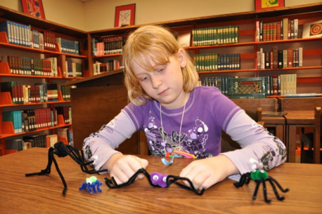 Emily Nodine, 9, adjusts the legs of a spider she crafted during a Magic Tree House book club meeting at the Thomas Lee Hall Library, Fort Jackson, S.C. The book club is part of the EDGE! program, an Army Family Covenant initiative.