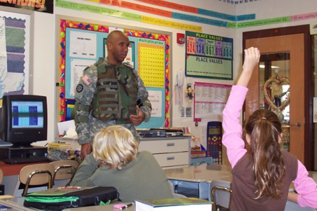 A Soldier speaks to school children about Army life during a Veterans Day event.