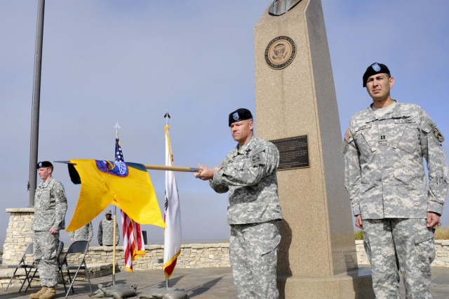 Col. Gregory Bowen unfurls the new unit guidon for Detachment One, 100th Missile Defense Brigade (Ground-based Midcourse Defense) in front of the Ronald Reagan Missile Defense site during the 100th MDB activation and change of command ceremony May 13, 201