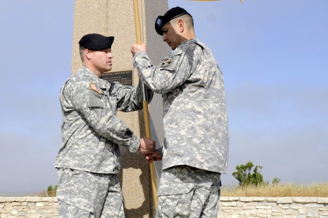 Col. Gregory Bowen hands the guidon to Capt. Orlando Cobos, signifying his assumption of command, in front of the Ronald Reagan Missile Defense site at Vandenberg Air Force Base during the 100th Missile Defense Brigade (Ground-based Midcourse Defense) act