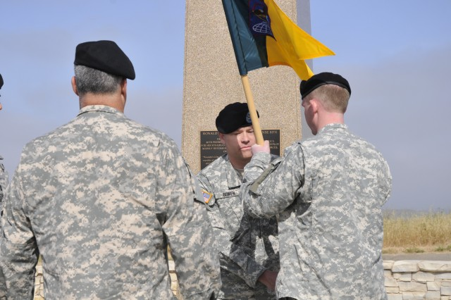 Col. Gregory Bowen hands the guidon to Capt. William Scott Palermo, signifying his assumption of command, in front of the Ronald Reagan Missile Defense site at Vandenberg Air Force Base during the 100th Missile Defense Brigade (Ground-based Midcourse Defe