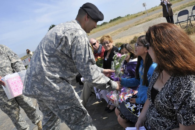 Outgoing commander, Capt. Orlando Cobos, hands flowers to his daughters, America and Reagan, at the Ronald Reagan Missile Defense site at Vandenberg Air Force Base during the 100th Missile Defense Brigade (Ground-based Midcourse Defense) activation and ch