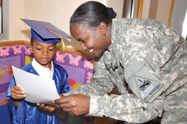 Jalen Custard, whose mother is on a 15-month deployment, shows his graduation certificate to his second-tier guardian, Staff Sgt. Juanita Sealey after successfully completing the Strong Beginnings program at USAG Wiesbaden, Germany.