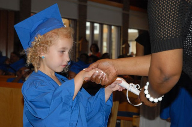 Cheyanne Norman, 4, receives her Strong Beginnings graduation diploma from lead teacher Debra Asberry at Fort Jackson, S.C.'s Main Post Chapel. Cheyanne was one of 40 preschoolers in the program.