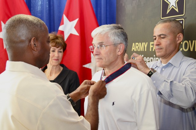 Retired Gen. George W. Casey Jr. is presented the Order of the White Plume by Maj. Gen. Reuben Jones and FMWRC Command Sgt. Maj. Abe Vega, as his wife, Sheila Casey, looks on.