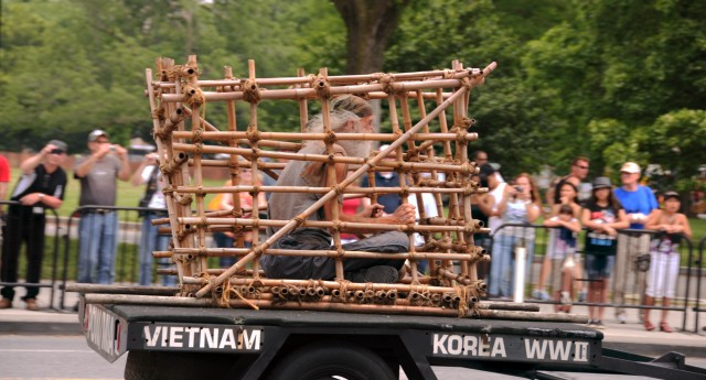 A man sits in a tiger cage during Rolling Thunder