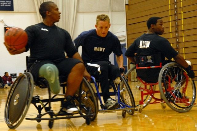 Spcs. Craig Smith (left) and Filipe Hill block a Navy competitor from the ball during wheelchair-basketball preliminaries at the 2010 Warrior Games in Colorado Springs, Colo.