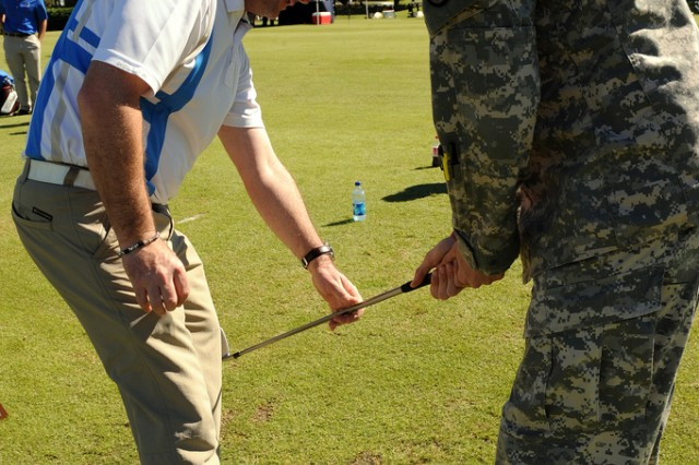 PGA Tour golfer Rory Sabbatini works with Spc. Brandon Cornwell of the 53rd Infantry Brigade in Cocoa Beach, Fla., during an Army Family and Morale, Welfare and Recreation Command golf clinic for Warrior Transition Unit Soldiers and veterans at the Osprey