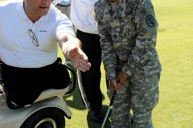 First Swing instructor Marty Ebel of the National Amputee Golf Association works with Staff Sgt. Jameka Promise of the Warrior Transition Unit in Orlando during an Army Family and Morale, Welfare and Recreation Command golf clinic at the Osprey Golf Cours