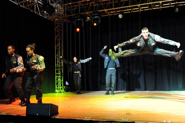 """Staff Sgt. La'Brenza McDonald of Fort Leavenworth, Kan., and Spc. Belita Ford of Washington, D.C., work on their dance steps while Pfc. Andrew Enriquez of Athol, Idaho, soars high above the stage to """"I've Got a Feeling"""" during rehearsal for the 2010 U.S."""