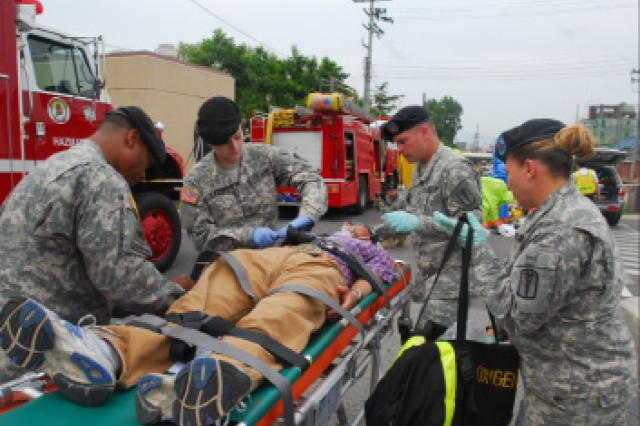 Medics respond to a simulated chemical attack at Camp Walker Community Activity Center May 25. Casualties were evaluated and treated on site and then evacuated by ambulance to appropriate medical facilities for further treatment.