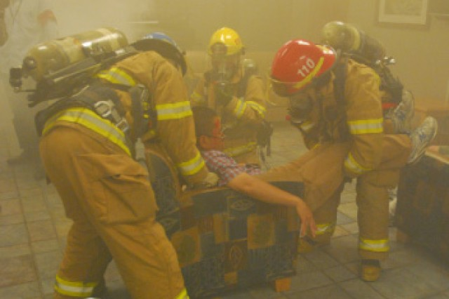 Firefighters from the Camp Walker Fire Station 1 evacuate casualties from simulated chemical attack at the community activity center May 25. Those wounded were then treated by medical personnel and then taken to medical facilities for further treatment.