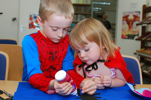 Spence Taylor, 7, glues a spider onto his Spiderman costume cape while his sister, Samantha, 2, looks on during Free Comic Book Day at the Patch Library May 21. The library offered free comic books, crafts, a costume contest and a chance for patrons to ta