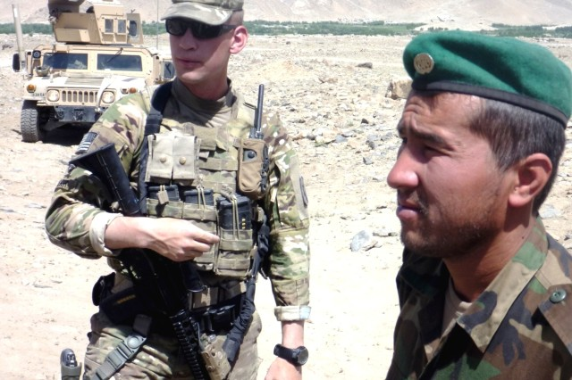 Sgt. Bob Brewer meets with an Afghan soldier at a checkpoint in the Musahi area of Afghanistan.