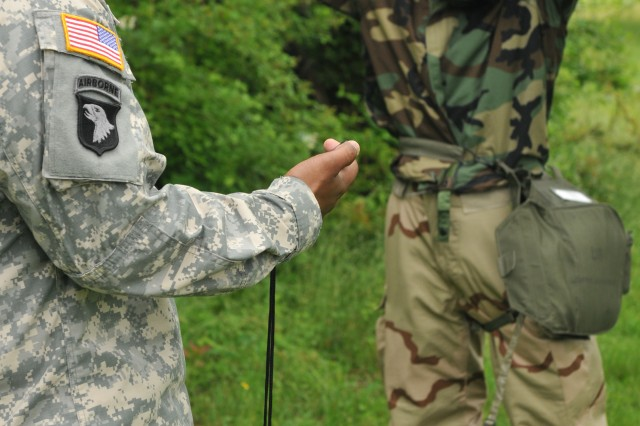 Spc. Darren R. Brons, junior enlisted winner of First Army's 2011 Best Warrior Competition, dons his protective mask for time during the Warrior Training task event. Brons will represent 1A at the Forces Command competition in July.