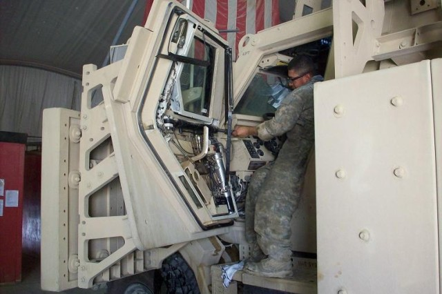 Contingency Operating Base Adder, Iraq – Spc. Luis Reyes from Bravo Field Maintenance Co., 215th BSB, 3rd BCT, 1st Cav. Div., replaces hydraulic fluid on the door of a Caiman during its annual maintenance services May 22, 2011.