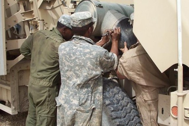 Contingency Operating Base Adder, Iraq – Spc. Dante Battle, Spc. Terrance Carter and Spc. James Edgington from Bravo Field Maintenance Company, 215th Brigade Support Battalion, 3rd Brigade Combat Team, 1st Cavalry Division, work together to replace an alt