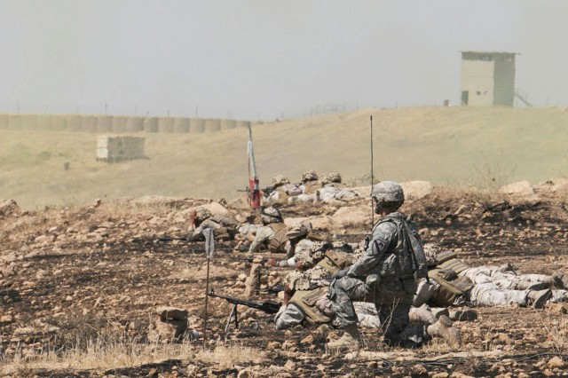 CONTINGENCY OPERATING SITE MAREZ, Iraq - Lt. Col. John Cushing, commander, 1st Sqdn., 9th Cav. Rgt, 4th AAB, 1st Cav. Div., kneels beside Iraqi soldiers providing support by fire during a battalion live fire exercise at GWTC, May 26, 2011.