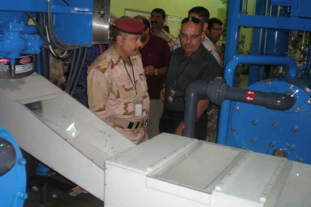 CONTINGENCY OPERATING BASE ADDER, Iraq - Iraqi Army Col. Muthana Subhi Abid AlJabbar, (left) and Lt. Col. Ammar Malek Farhood Hassan, (right) learn about the various ice making machines at the COB Adder Ice Plant during a tour May 28, 2011.