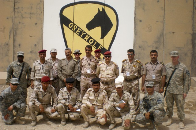 CONTINGENCY OPERATING BASE ADDER, Iraq – Iraqi Army Col. Muthana Subhi Abid AlJabbar, (4th from right, back row), with his fellow Iraqi officers and Soldiers, pose for a photograph in front of the 215th BSB headquarters building.