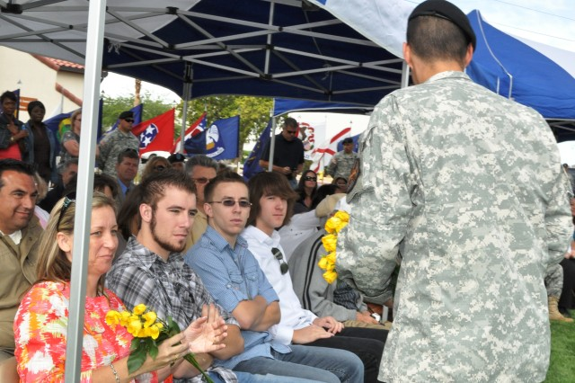 Karol Pinkerton, spouse of incoming Fort Irwin Garrison commander Col. Kurt J. Pinkerton, receives yellow roses from Sgt. Enrique Villareal, National Training Center Military Police Company, during a change of command ceremony between Pinkerton and outgoi