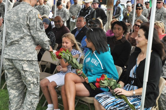 June Chevallier, spouse of outgoing Fort Irwin Garrison commander Col. Jim Chevallier, smiles as she and her daughters receive red roses during a change of command ceremony between Chevallier and incoming Garrison commander Col. Kurt J. Pinkerton on Wedne