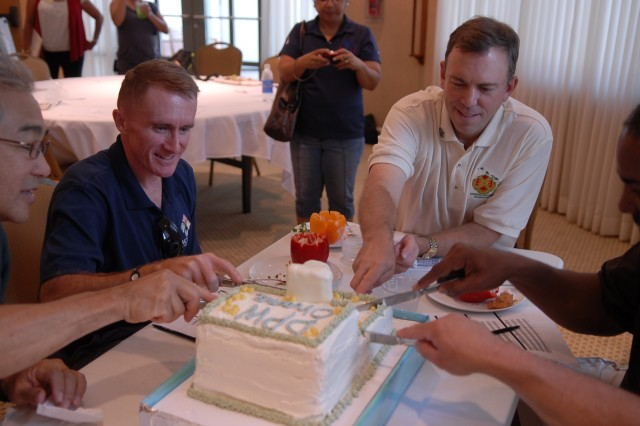 SCHOFIELD BARRACKS, Hawaii - Col. Douglas Mulbury (left), commander, USAG-HI, and James Duttweiler, deputy garrison commander, USAG- HI, cut the DPW/toilet cake, submitted by Lena Stoychett, DHR, which placed first in the dessert section at the garrison o