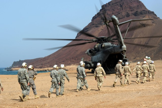 Soldiers, Marines, sailors and airmen walk toward a waiting CH-53E Super Stallion after attending a memorial ceremony at the wreckage site of two downed helicopters off the northern coast of Djibouti, May 30, 2011.
