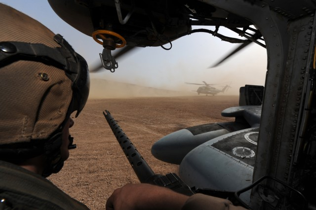 A gunner aboard a CH-53 Super Stallion with Marine Heavy Helicopter Squadron 464 watches as another helicopter takes off on the north coast of Djibouti, May 30, 2011.