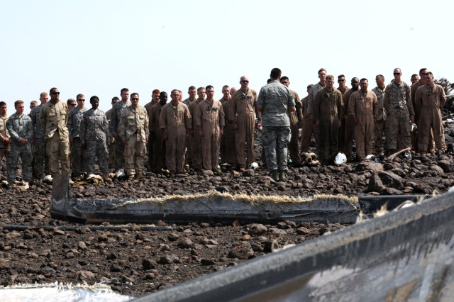 Soldiers, sailors, airmen and Marines stand together as U.S. Air Force Chaplain (Capt.) Aaron H. Klaves, assigned to Camp Lemonnier, Djibouti, conducts a memorial ceremony at the wreckage site of two downed helicopters off the northern coast of Djibouti,