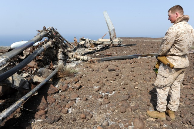 U.S. Marine Corps Cpl. Daniel Rodgers pauses to reflect at the wreckage of two downed military helicopters near the northern coast of Djibouti during a Memorial Day commemoration, May 30, 2011.