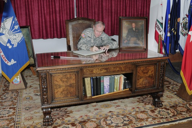 """Gen. Martin E. Dempsey, Chief of Staff of the United States Army signs a guestbook, while sitting at the """" George  S. Patton's desk,"""" at the 7th U.S. Army Noncommissioned Officer Academy in Grafenwoehr, Germany, June 1-2.  While at the Joint Multinational"""