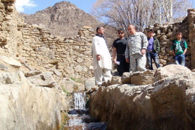1st Lt. Hakan Togul, Panjshir Provincial Reconstruction Team civil affairs lead, speaks with a village elder about a project to bring drinking water to Astana Village in Bazarak Municipality, Afghanistan March 24, 2011.