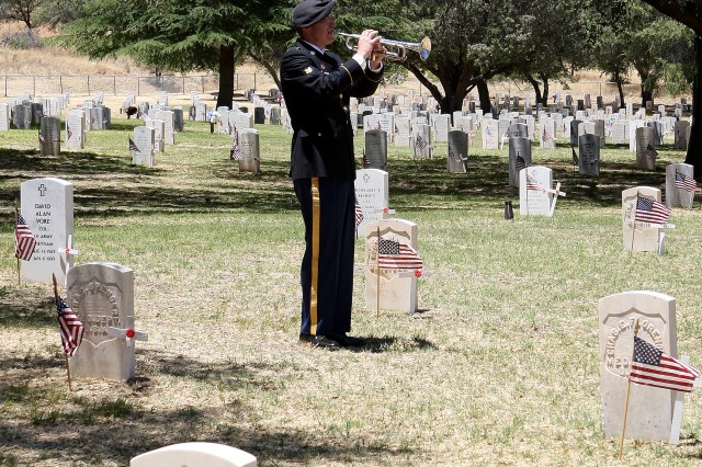 "Spc. George Weber, 36th Army Band, plays ""Taps"" Monday during the Memorial Day Observance at the Old Post Cemetery on Fort Huachuca."