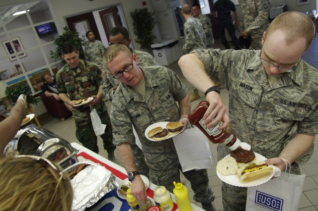 Airman 1st Class Mike Mason (right) and Airman Vicente Osorio, Air Force 336th Training Squadron Detachment Two, treat themselves to free hamburgers at the Fort Meade USO's second annual Service Member Appreciation Barbecue at the Freedom Center barracks