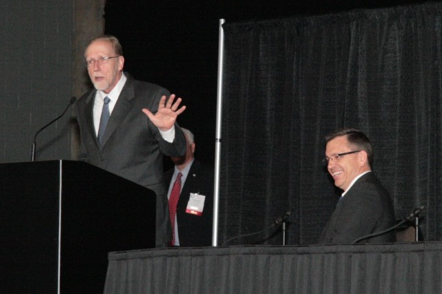 U.S. Reps. Dave Loebsack of Iowa (podium) and Bobby Schilling of Illinois (seated), provided congressional updates to attendees of the 2011 Midwest Small Business Symposium, held May 17-18 at the iWireless Center in Moline, Ill. (Photo by Liz Adrian, ASC Public Affairs)