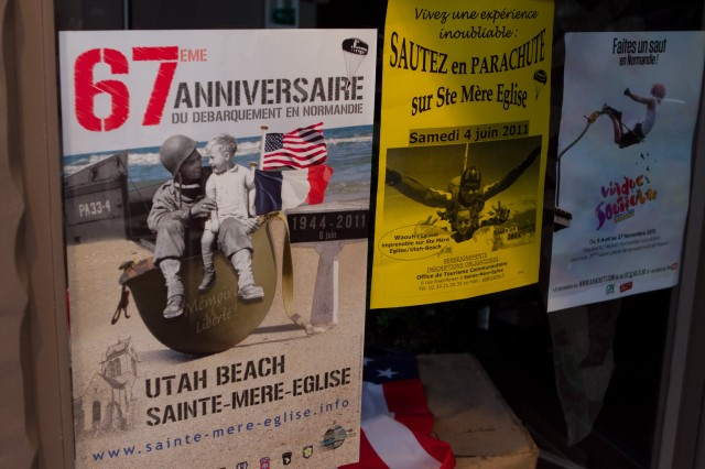 A poster advertising the 67th Anniversary of the World War II Allied invasion of France appears in a storefront in Sainte Mere Eglise, a Norman village liberated by the 82nd Airborne Division.  This year, as in years past, paratroopers with the storied All American division participated in memorial ceremonies and parachute into a nearby field, re-enacting the jump the division made in the predawn hours of D-Day, June 6, 1944.