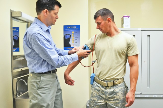 Michael Bergeron, clinical pharmacist, hooks up Sgt. David Callahaun up to an Ambulatory Blood Pressure device, which automatically records patients' blood pressure readings continually for 24 hours.