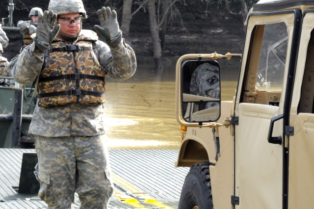 Spc. Aaron Ybaro, a bridge crewmember with the 502nd Multi-Role Bridge Company, directs a Humvee onto an Improved Ribbon Bridge. The Soldiers used the Humvee to test if the IRB was properly assembled.