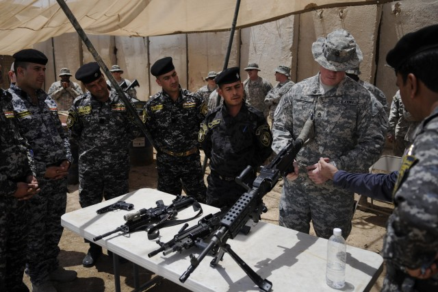 Sgt. 1st Class Clay Rose, with 2nd Advise and Assist Brigade, 1st Infantry Division, gives instruction on range and weapon safety to Iraqi Federal Police, May 16, 2011, at Joint Security Station Loyalty, Iraq.