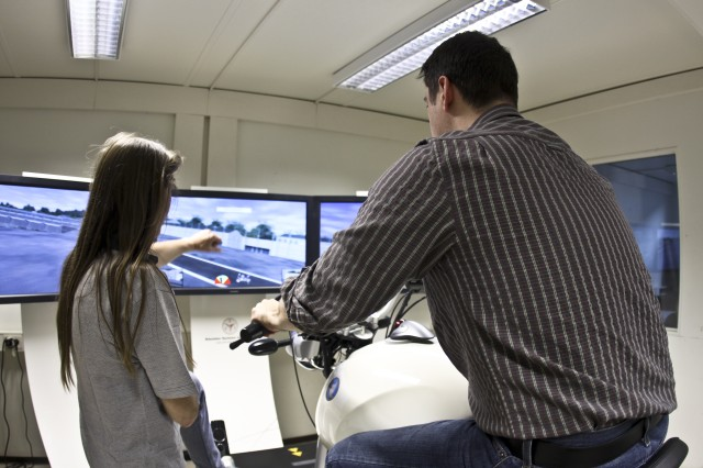 Ross Goodspeed, U.S. Army Corps of Engineers Europe District records manager, receives guidance from Motorcycle Safety Foundation instructor Nicole Kruger during the Emergency Situations Course offered at McCully Barracks in Germany. The simulator training course is designed to improve both novice and experienced motorcycle drivers' skills without risk of injury.  Facility renovations were managed by the district. The simulator is the only one of its kind in U.S. Army Europe.