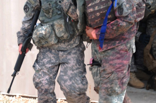 Spc. Christopher Gifford moves a casualty able to walk from a building to the military ambulance to depart of the site.